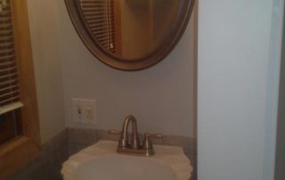 bathroom with shell sink & circle mirror